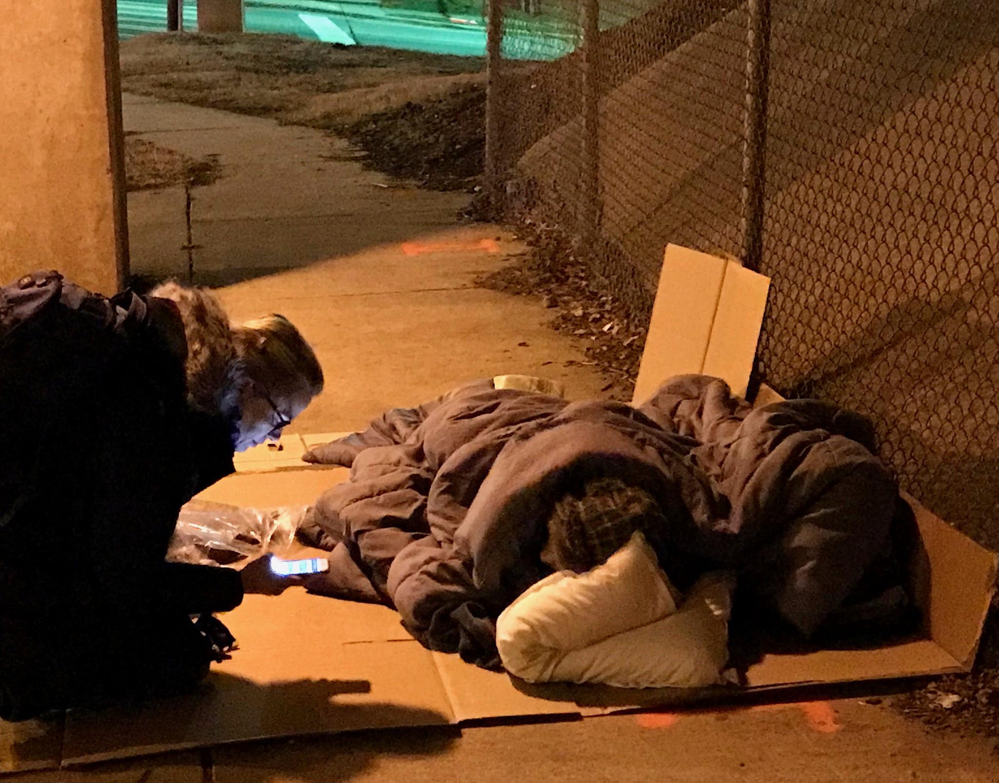 A woman kneeling next to a homeless man sleeping outside