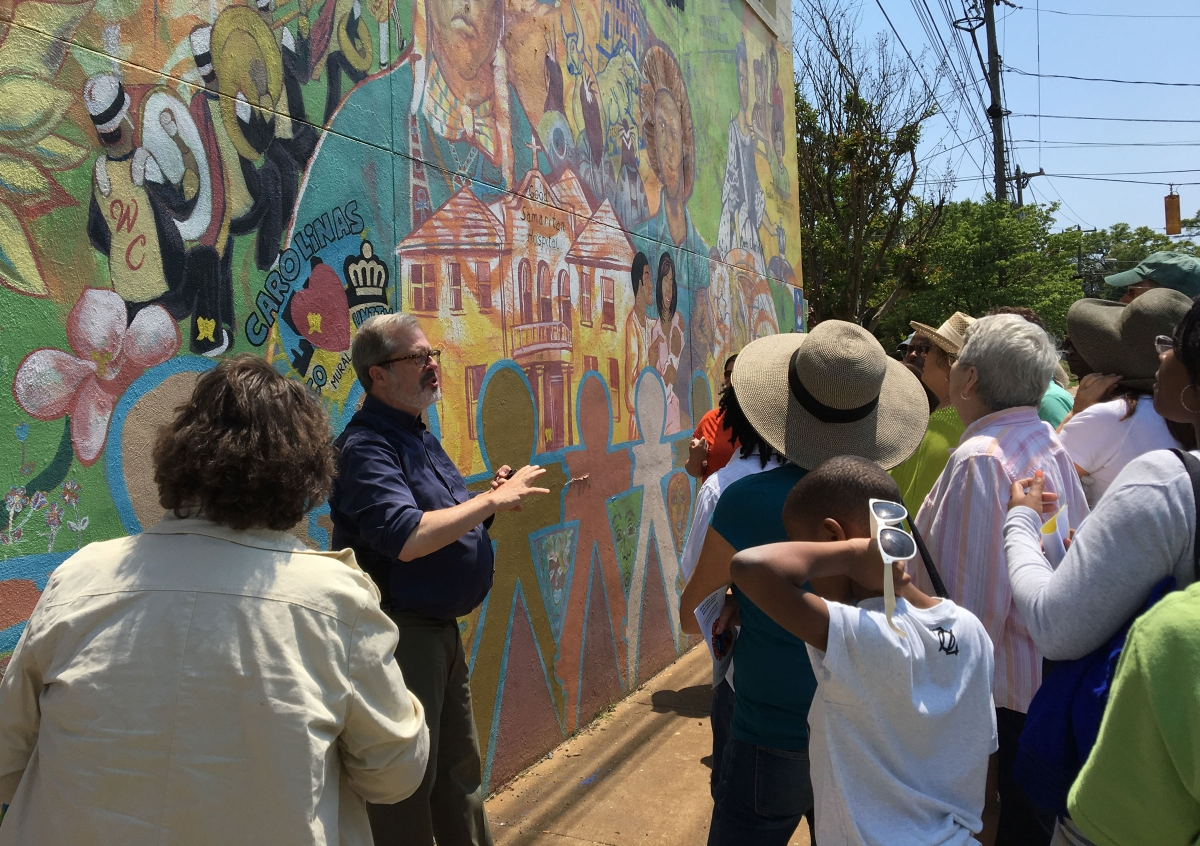 Local historian Tom Hanchett discusses a mural with participants in a 2018 Charlotte City Walk.