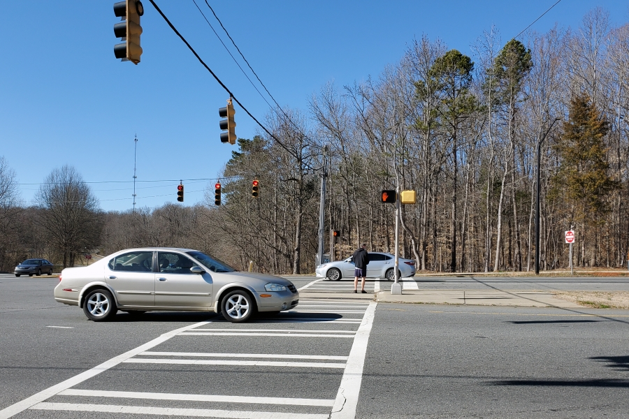A pedestrian waits to cross the road at a busy north Charlotte intersection
