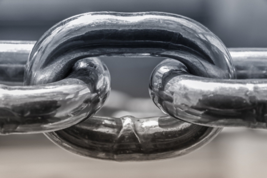 A close up of three linked metal chains.