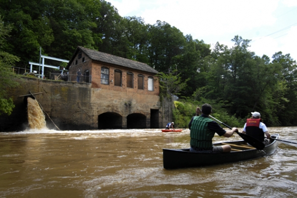 Paddlers on the South Fork River look at a small, independent hydro power generating plant on the river.