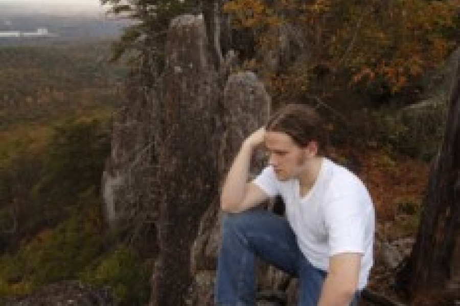 A young man enjoys the view after climbing Kings Pinnacle Trail in Crowders Mountain State Park.