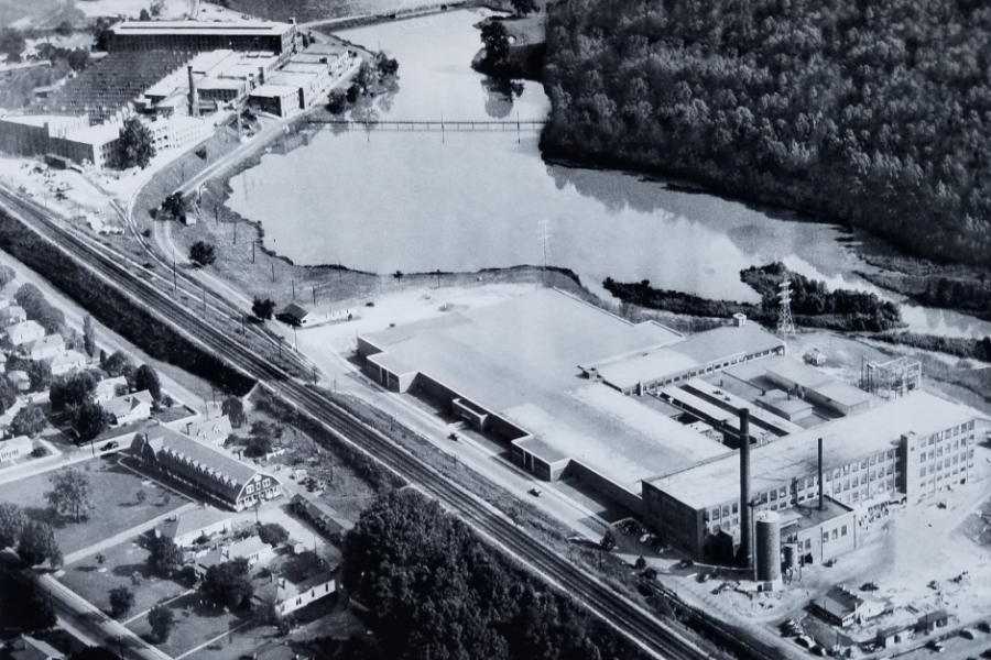 """The Mays and Mayflower mills in Cramerton, both of which closed in the 1970s. One was subsequently demolished, the other destroyed by fire. In this photo, the South Fork of the Catawba River has been diverted to form a wide pool to serve the mills' dyeing and finishing operations. Waste dumped in the water gave it the nickname """"Rainbow River"""" for decades. To the left of the train tracks, a dormitory for single, male mill workers is visible; above those, mill houses can be seen. Photo courtesy the Millican P"""