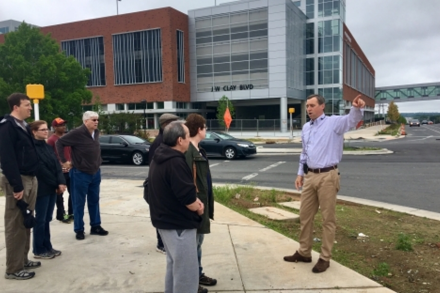On a May 13 walk, leader Tobe Holmes of University City Partners, in front of a new Charlotte Area Transit System parking deck, describes changes that will make North Tryon Street a more pedestrian-friendly area when the Blue Line Extension opens March 2018. Photo: Mary Newsom