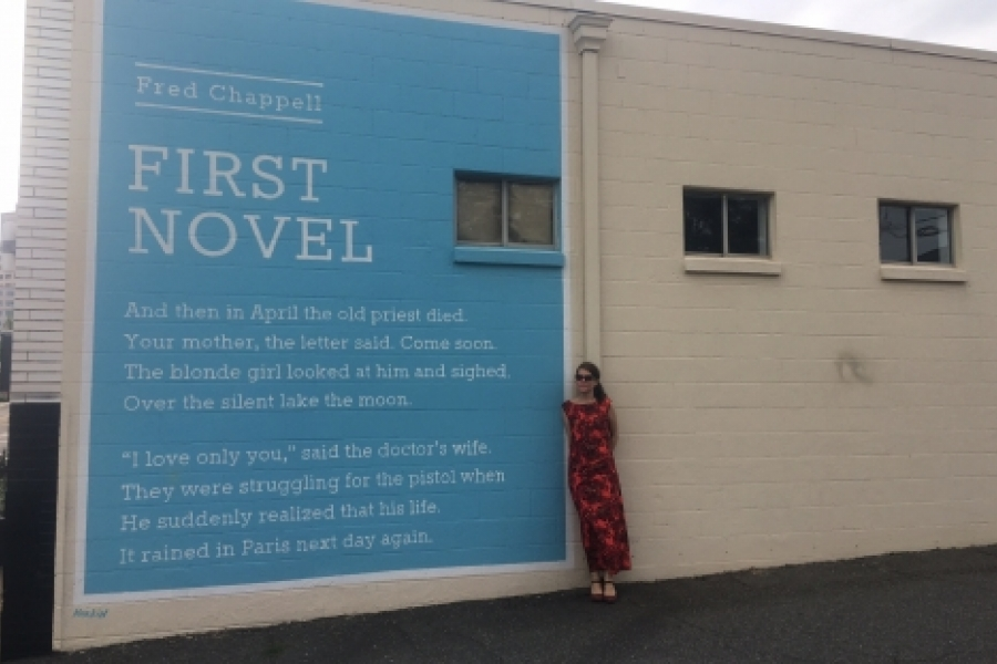 Walk leader Amy Bagwell, artist and poet, in front of one of the 20 Wall Poems painted around Charlotte. The poem by Greensboro poet Fred Chappell at East Ninth and North Brevard streets was on the May 17 Uptown Wall Poems walk. Photo: Mary Newsom