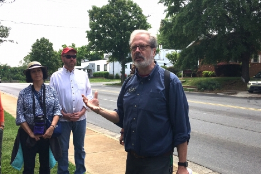 Walk leader Tom Hanchett, on a May 13 walk, describes the historic Excelsior Club behind him on Beatties Ford Road, a nightclub that opened in 1944 and hosted entertainers Nat King Cole and Louis Armstrong. as well as hundreds of community events. Photo: Mary Newsom