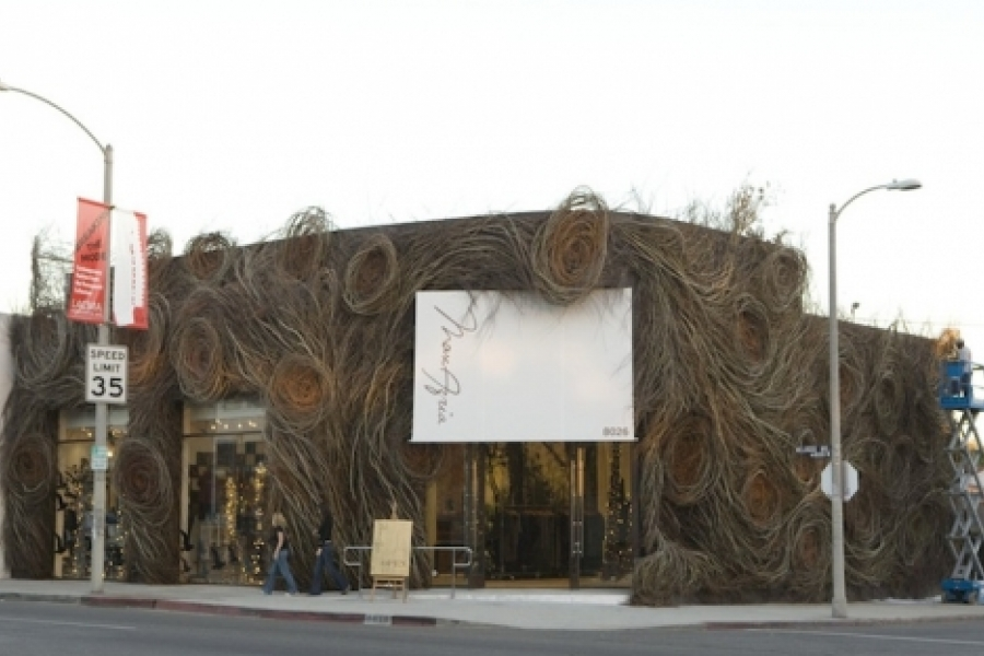 """Patrick Dougherty's """"Just For Looks"""" (2006) is a willow sculpture enveloping the Max Azria Boutique in Los Angeles, Cal. A dramatic swath of newly cut saplings was woven up and around the building, like upholstery in its own version of paisley cloth. Photo: David Callicchio"""