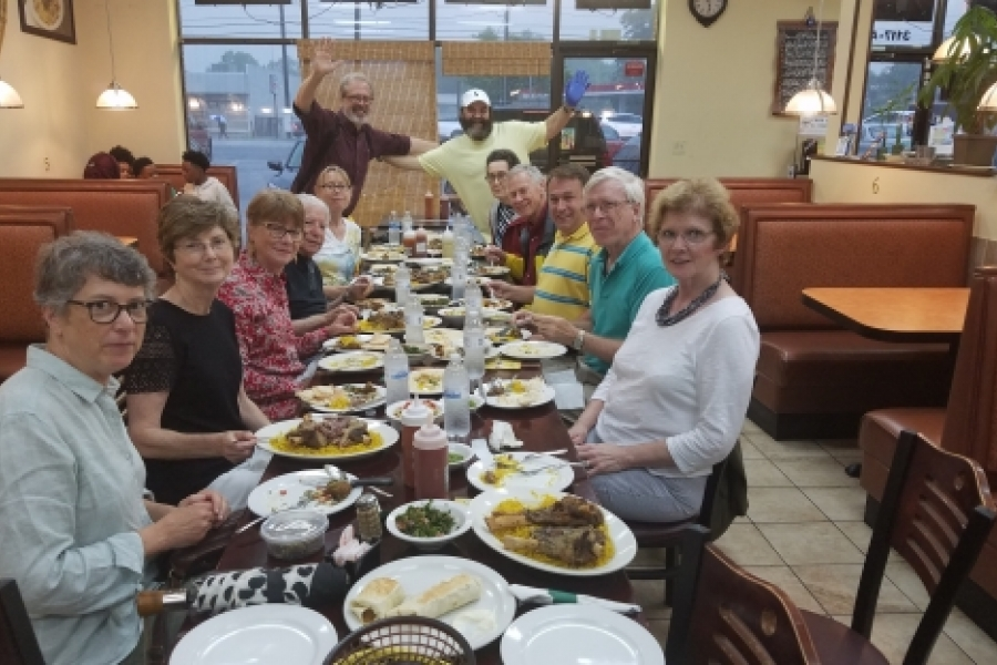 The first walk, May 1, was a Munching Tour of east Charlotte, led by historian Tom Hanchett, at far end of table, left. The group is at La Shish Kebob, with owner Izzat Freitekh, at end of table, right, waving with blue glove. Photo: Angelique Gaines.