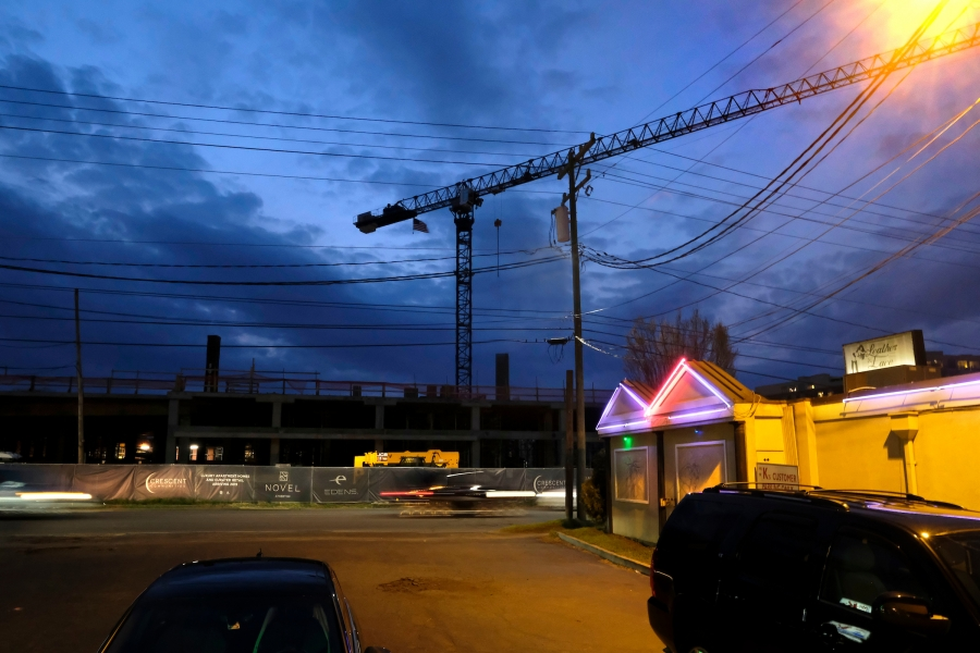 "Neon lights from the decades-old South Boulevard adult entertainment venue, Leather and Lace, illuminate the parking lot of beloved burger and ice cream shop, Mr K.s, which dates to 1967. In the background, a short walk from the East-West Boulevard Station, Crescent Communities' Novel Atherton ""luxury apartment homes"" is set to open in 2019. Photo: Nancy Pierce"