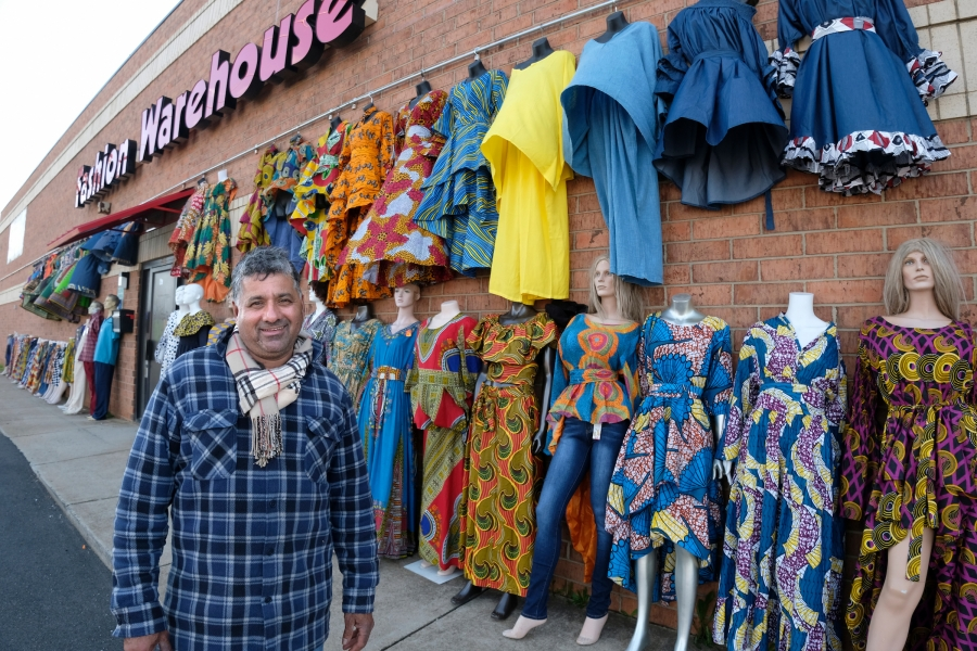 Owner George Saini bought land next to his Fashion Warehouse for more parking when the light rail right-of-way and sidewalk took most of the existing parking lot in front of the building, near the Tom Hunter Station. Each evening, it takes him about a half hour to take all the clothes back inside his store. Photo: Nancy Pierce