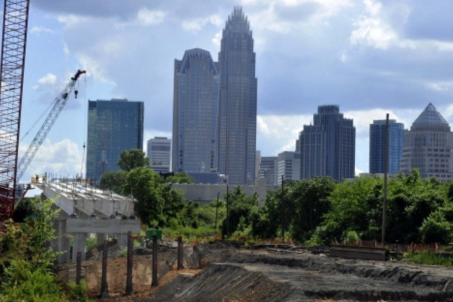 The uptown Charlotte skyline, seen from the Blue Line Extension bridge over the CSX freight line at East 16th Street. The crane lifts in wooden forms, to form concrete for the bridge overhang. Photo: Nancy Pierce