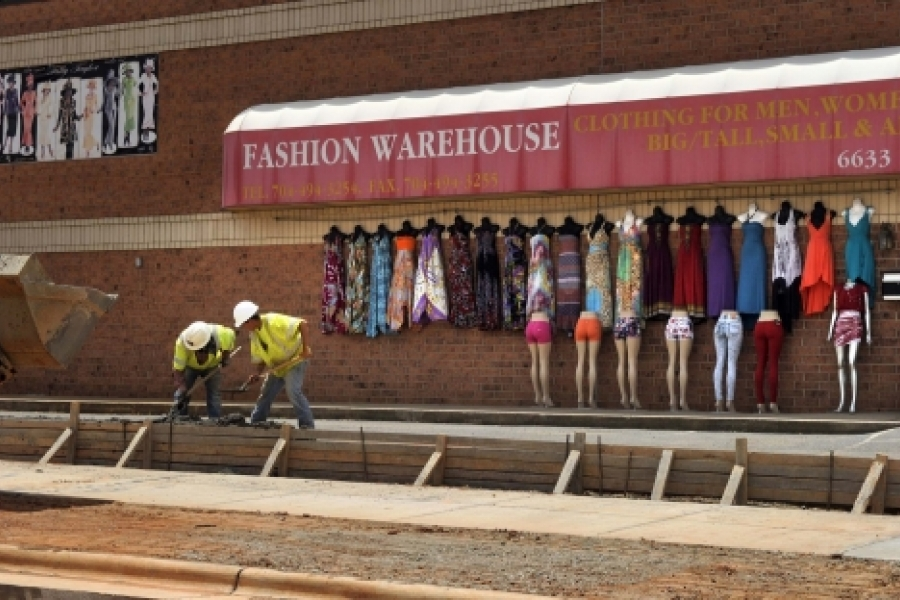 """Crews work on a parking lane, curb, gutter and sidewalk in front of Fashion Warehouse, North Tryon Street at Tom Hunter Road. Owner George Saini, who hangs clothes outside """"New York style,"""" says he is happy the construction will provide more parking and a more walkable approach to his store. Photo: Nancy Pierce"""