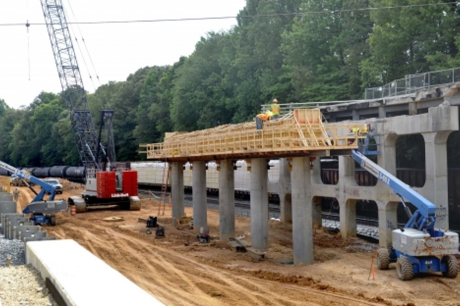 This is the Eastway Drive bridge being built over the Norfolk Southern and Blue Line Extension tracks. The work closed Eastway Drive, a major thoroughfare, in May 2014. It was to have reopened in December 2014 but now it won't open until September. In this June photo, workers install wooden forms to cap the piers before setting down the bridge deck. Photo: Nancy Pierce