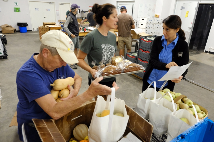 From left: Volunteer Beth Whitman packs produce boxes, Mandy Davis, co-director of Sandhills Farm-to-Table, and  Mireia Brunner, owner of Aberdeen Bakehouse. Sandhills Farm-to-Table subscribers can order bread and pastry from Mireia's shop online for delivery. Photo: Nancy Pierce