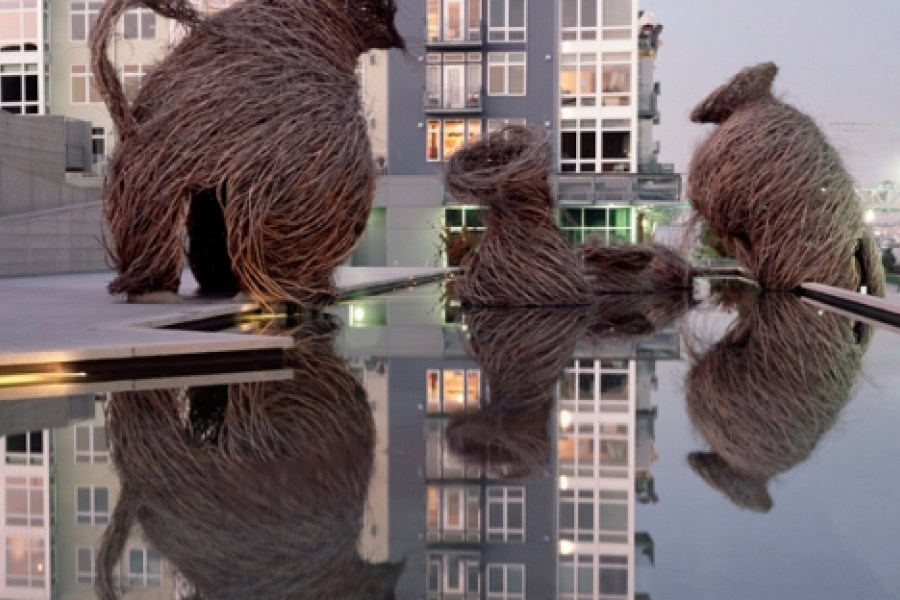 """Patrick Dougherty's """"Call of the Wild"""" (2002), at the Museum of Glass in Tacoma, Washington. Nature's fragility in the face of pollution, global warming, and species loss is illustrated in garden urns cast as an illusion of wild nature. Photo: Duncan Price"""