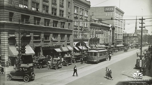 Cars and a trolley line the street as three people cross the street in Downtown Charlotte in 1926.