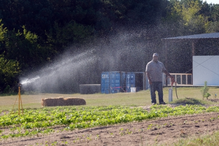 Davon Goodwin watches a sprinkler at the Sandhills AGInnovation Center demonstration farm east of Charlotte.